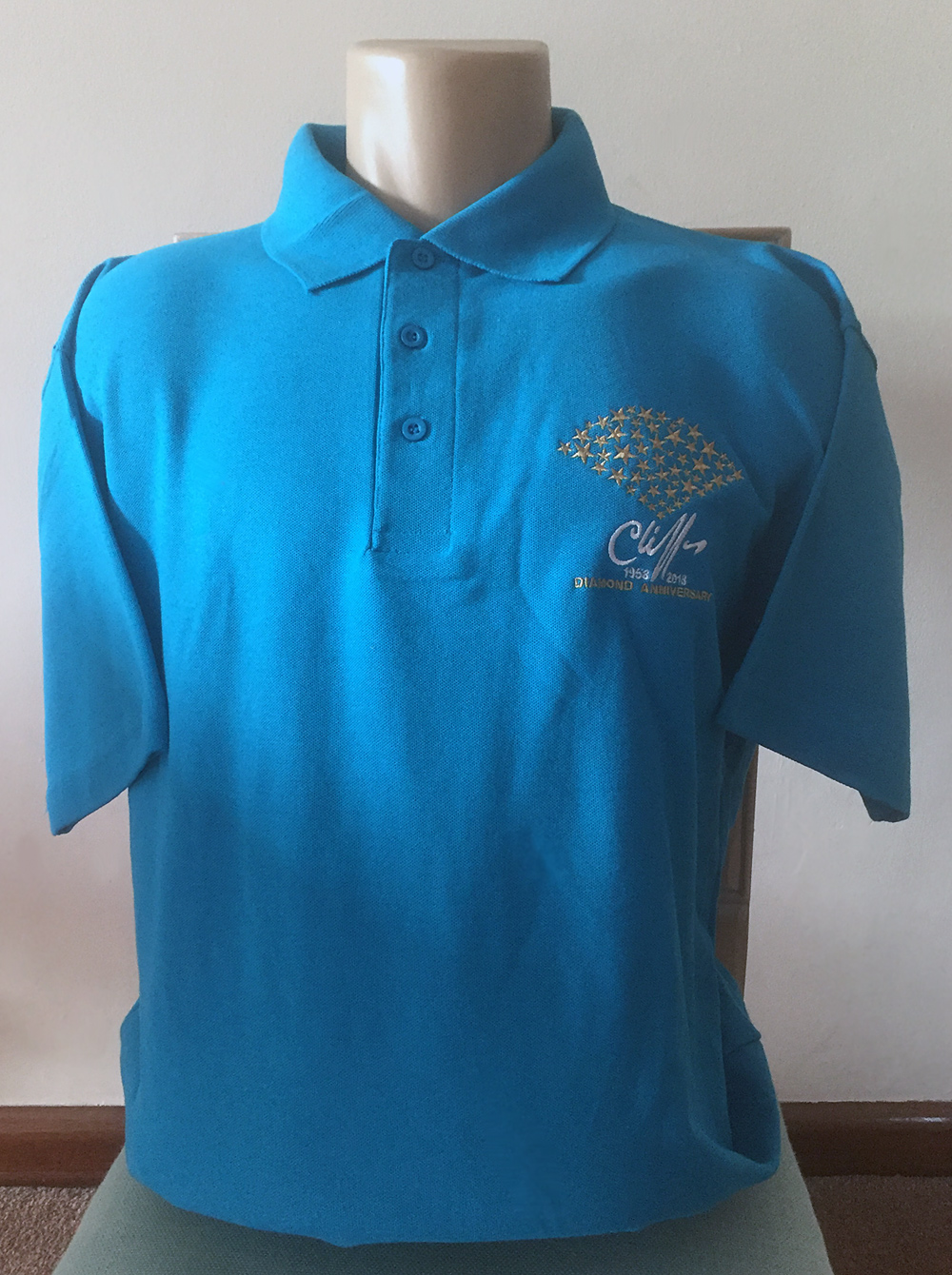 Cliff Richard polo shirt in blue with embroidered gold starburst diamond anniversary design